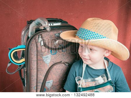 Child in Hat and Scuba mask near Suitcase looking left