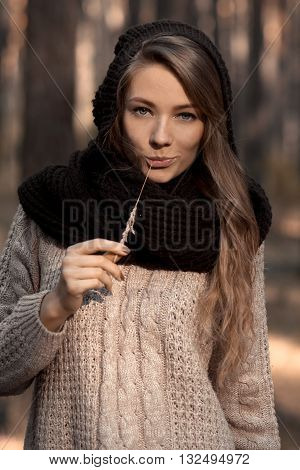 Close-up of fashionable model, glamorous girl in scarf and hat with straw in teeth, fingers, hands, mouth. Perfect sunny face with blue eyes. Sunny portrait of smiling girl. Creative idea. Autumn forest.