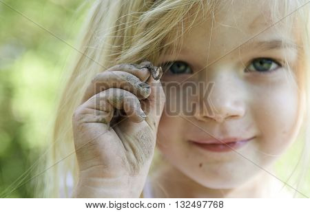 Four year old child blond girl holding a worm in the garden