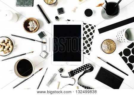 flay lay composition for bloggers artists magazines and social media. freelancer black style workspace with tablet black coffee sketchbook napkins ribbons paintbrushes on white background.