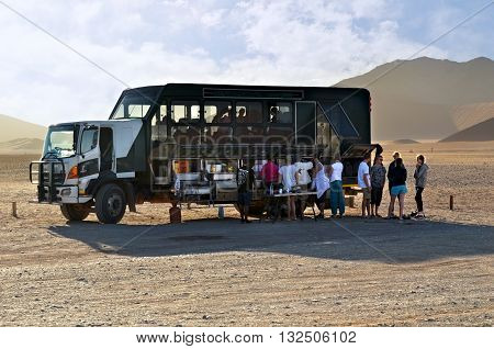 SOSSUSVLEI NAMIBIA - JAN 29 2016: Overland truck with tourist shown in Namibia at sunrise. Overlanding is self-reliant overland travel to remote destinations where the journey is the principal goal