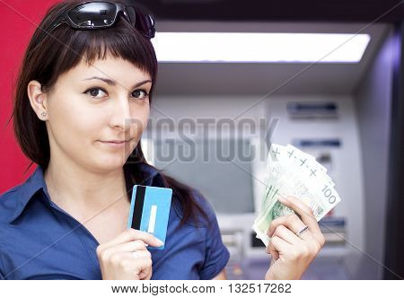 Beautiful woman using credit card she is withdrawing money from an ATM machine.