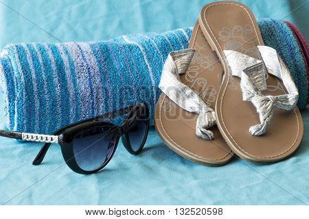 Beach towel with sunglasses and flip flops sandals
