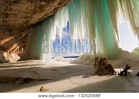 Grand Island in Winter - Lake Superior. A stump is the highlight in this cavern behind the Grand Island ice curtains on Lake Superior near Pictured Rocks National Lakeshore in Munising Michigan