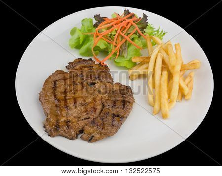 Pork steak served with french fries and salads to vegetables isolated on the black background with clipping path