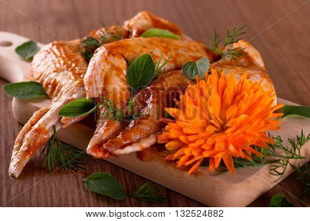 Three Marinated Chicken Wings With Marigold On Wooden Board