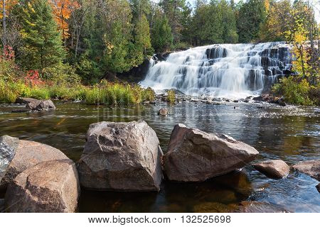 Bond Falls in Paulding Michigan is surrounded by vivid autumn colors. Bond Falls State Park can be found in the Upper Peninsula of Michigan