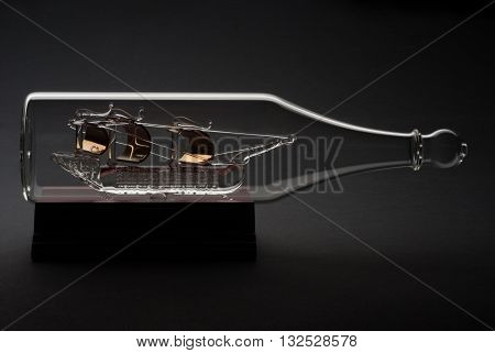 A Glass Caravel on a wood support in a black backgorund