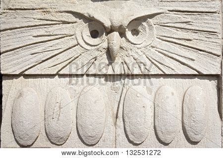 Ancient Owl Head Bas-Relief on the Wall. Architecture Details Close Up. Copy space for your text in the bottom half on wings.