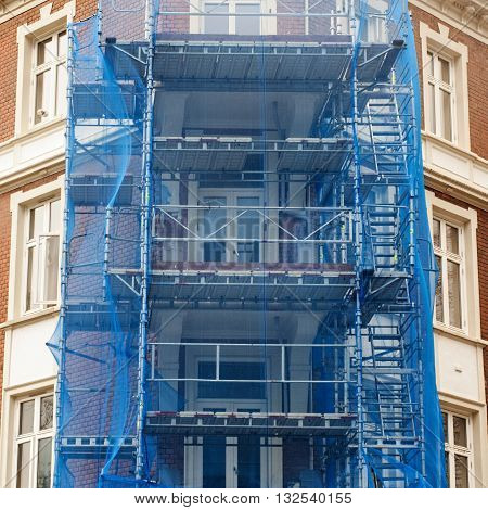 restoration facade of old house under blue net