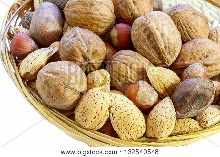 Mix of walnut brazilian nut hazelnut pecan almond. Isolated in white background cutout. Brown straw hand-made basket with round edge. Concept healthy food. Rich brown colors. Snack protein. Vegetarian food.