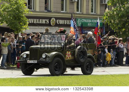 Donetsk People Republic Ukraine. 2016 May 9. - Russian military veterans of World War II riding in the old car along Artema street during Victory Parade in Donetsk. The crowd photographs show. Flowers Flags of Russia and DPR.