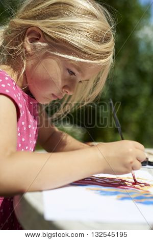 A girl painting with water colors (watercolors), painting a paper plate with watercolor paints outside in garden