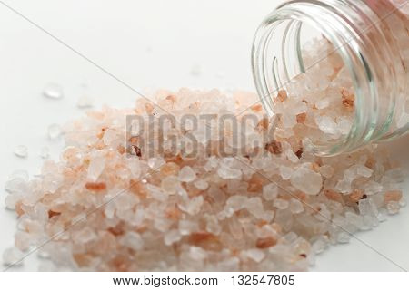 Himalayan pink salt in small jar of glass. Himalayan salt pile on white background. Pink crystal salt  isolated on white background. Close up Himalayan salt - pink and orange coarse crystals.