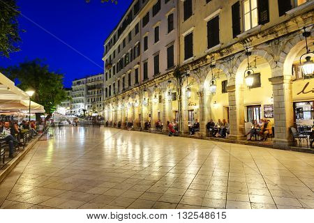 KERKYRA GREEES - MAY 14: The tourists are in cafes in Liston during sunset on May 14 2016 in Kerkyra Greece. Up to 16 mln tourists is expected to visit Greece in year 2016.