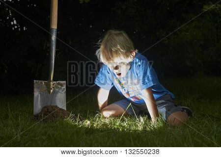 Child boy have unearthed a treasure in the grass, digging treasure