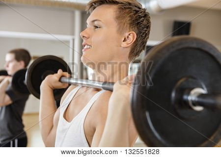 Handsome Man Lifting Barbell In Gym