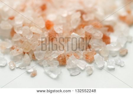 Pink Himalayan salt. Himalayan salt pile on white background. Pink crystal salt. Close up Himalayan salt - pink and orange coarse crystals.