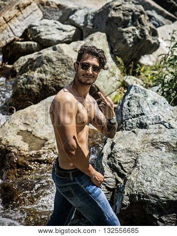 Athletic shirtless young man outdoor at river or water stream, looking at camera, doing middle finger gesture like Screw You