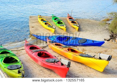 Multi-colored plastic kayaks arranged on a cement pier ready to be taken out on the water.