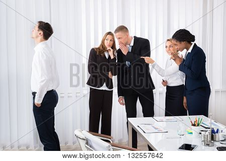 Businesspeople Gossiping Behind Young Colleague In Office
