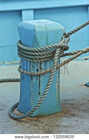 Blue fishing boat tied to land by a rope