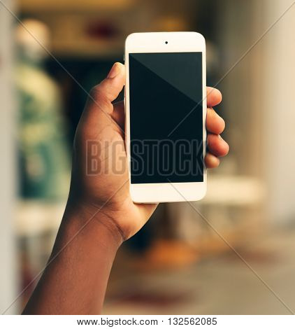 Mans hand shows mobile smart phone, blurred background