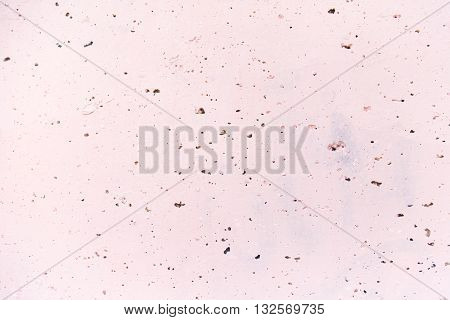 Vesicular rough holey porous texture light pink magenta wall close-up background