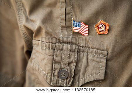 USSR & USA flag historic national emblem on a khaki shirt person chest: Stars and stripes hammer and sickle close-up. Partnership or confrontation