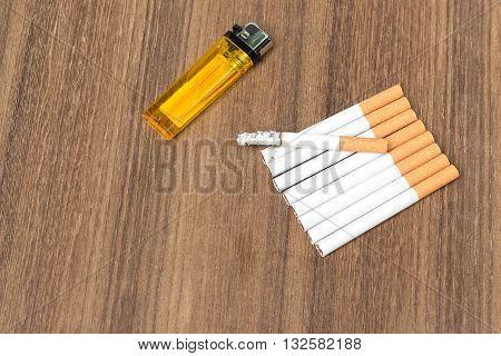 Tobacco and lighter burning cigaretter detrimental on wood background select focus front cigaretter