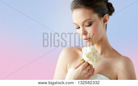 beauty, jewelry, people and luxury concept - beautiful asian woman or bride in white dress with peony flower and golden ring over rose quartz and serenity gradient background