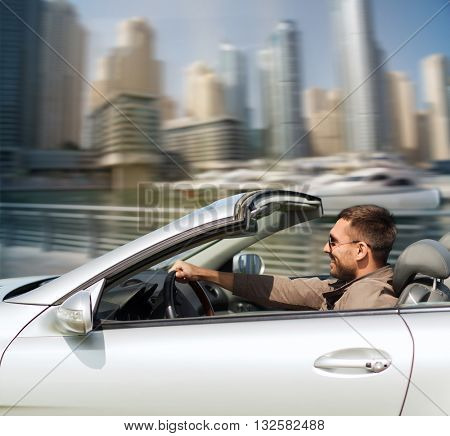 auto business, transport, leisure and people concept - happy man driving cabriolet car over dubai city port background