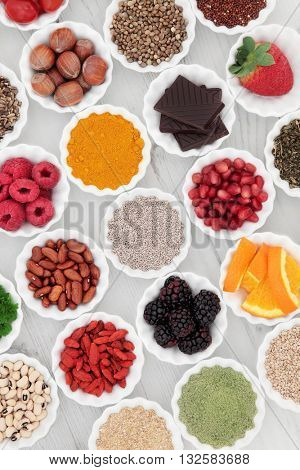 Health and superfood selection in porcelain crinkle bowls over distressed wooden background. High in vitamins and antioxidants. poster