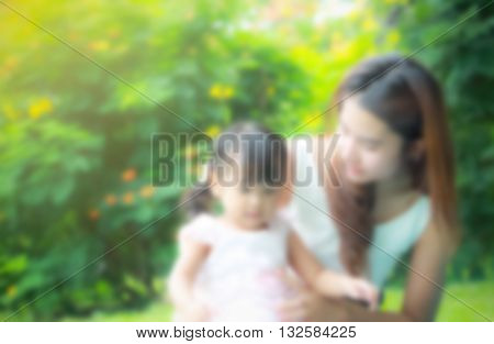 sweet dreamy and de-focused close up portrait of Asian mother take care young daugther in garden