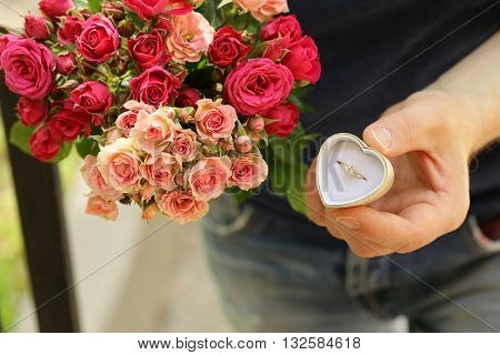 man with a bouquet of roses and a diamond ring, ready to make a proposal