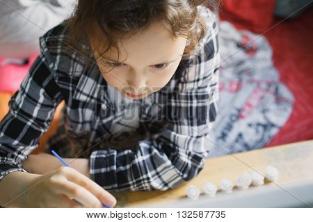 eight year old girl in a plaid shirt with enthusiasm that paints with a brush