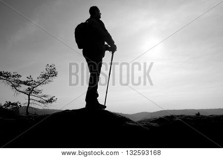 Tourist in windcheater with sporty trecking poles in hands stand on rocky view point. Spring sunny day. poster
