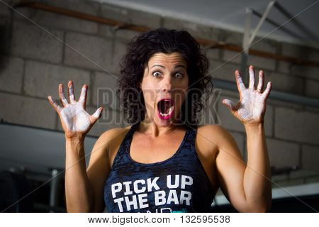 A weight lifting trainer feigns surprise as she holds up chalky hands.