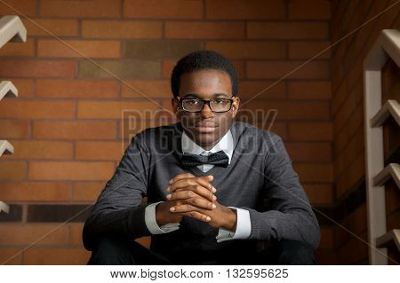 A confident african american teenager wearing a bowtie sits in front of a brick wall and leans forward resting on his knees.