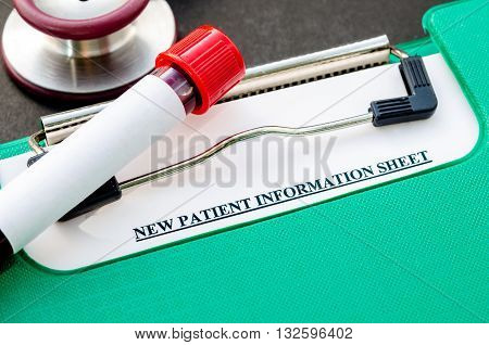 Sample blood in tube for test and New patient information sheet in file with stethoscope on black background.