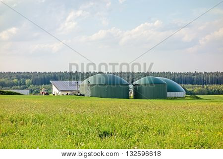 Heidenheim an der Brenz Germany - May 26 2016: Biogas plant barn with photovoltaics tractor aside green meadow in front