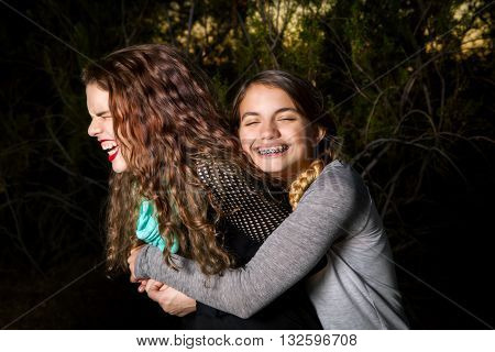 A younger sister hugs her older sibling from behind with a big loving smile and closed eyes. The older sister trys to get away also with closed eyes and disgusted face yet trying not to laugh.
