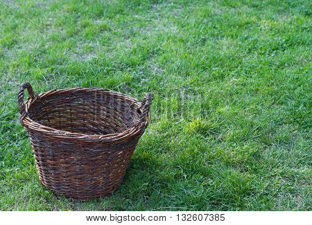 horizontal top view of a wood basket standing on green grass on a field