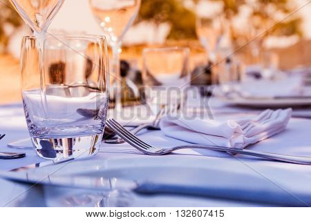 Outdoor lunch table setting with cutlery and glasses