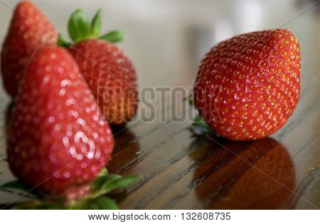 overripe organic strawberry on a wooden table