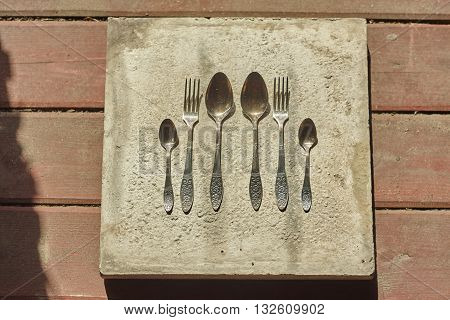 two big spoons forks and little spoons on concrete and wood floor