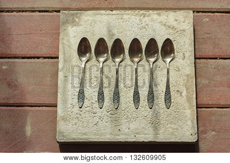 six big spoons on concrete and wood floor