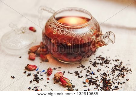 The Dry Red Small Roses with Black Tea in the Glass Teapot,Tea Drinking,Aromatized Flowers, Linen Tablecloth;Toned