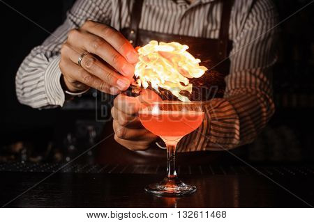 The bartender makes flame fromorange zest above cocktail