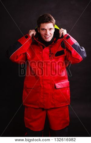 Young man putting on hood. Male dressed in weatherproof clothing. Adventure outdoor action danger concept.